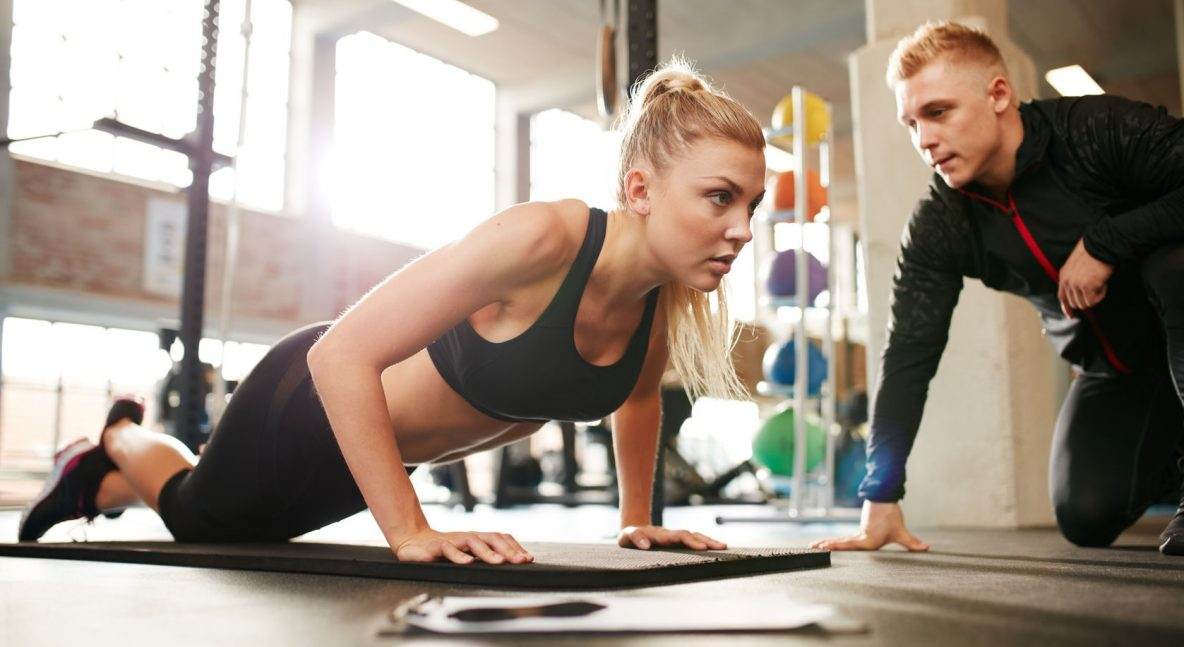 48840731 - fitness woman exercising with fitness trainer in gym. woman doing push ups exercise with her personal trainer at health club.